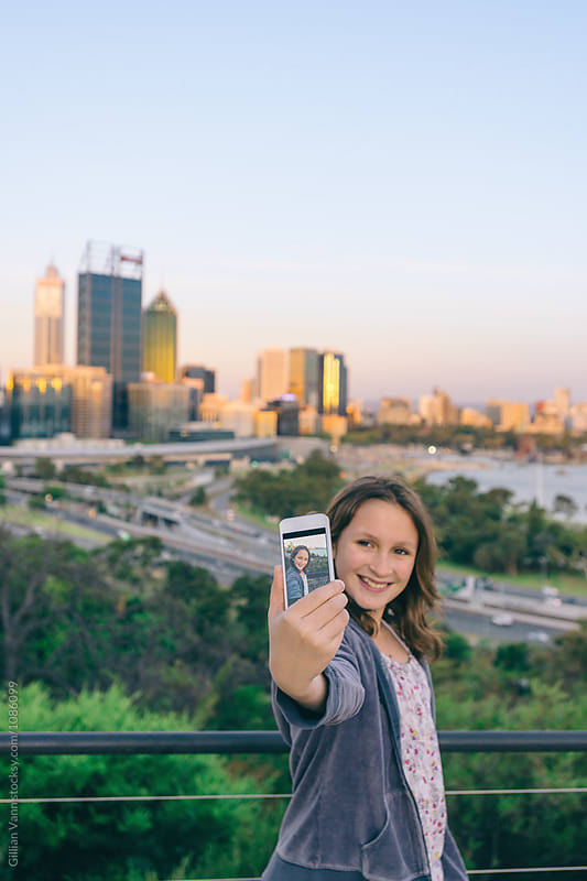 teenage girl taking a selfie on her mobile phone in front of Perth city by Gillian Vann for Stocksy United