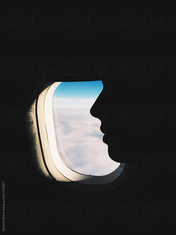 Young woman portrait against porthole on the plane by GIC for Stocksy United