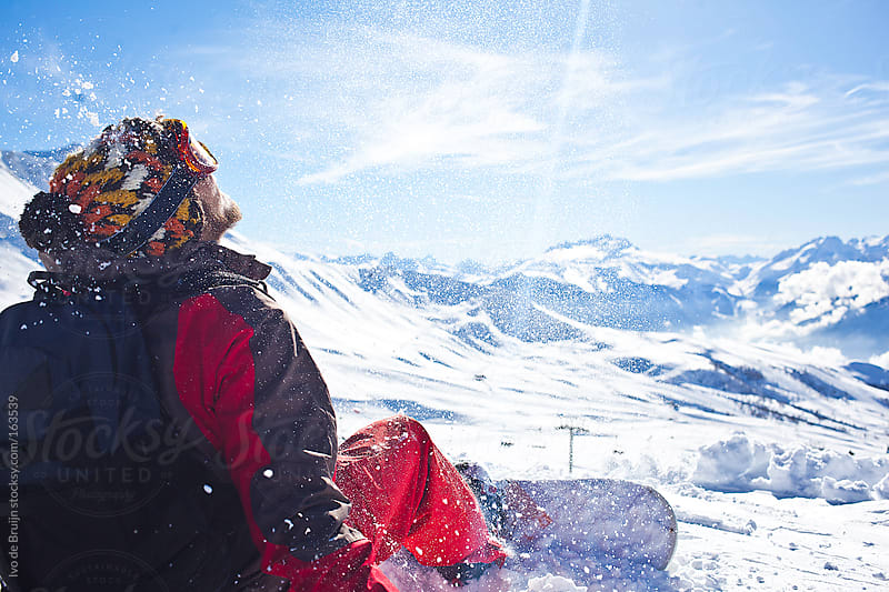 Snowboarder sitting on the slope of a resort with snow flying around him by Ivo de Bruijn for Stocksy United