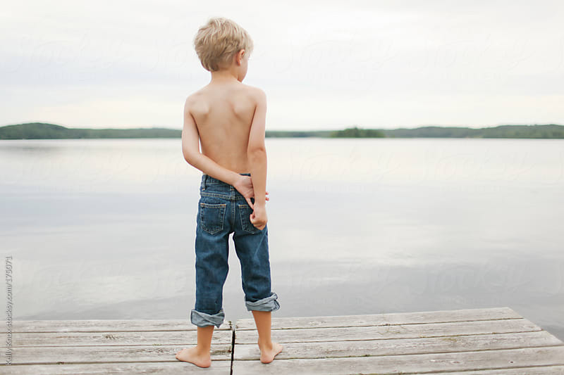 boy standing at the end of a pier by Kelly Knox for Stocksy United