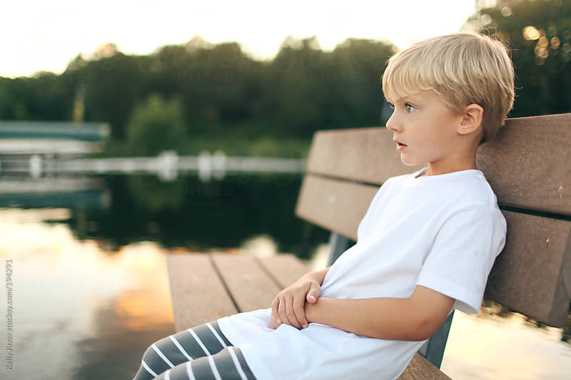 child sitting on a pier at sunset by Kelly Knox for Stocksy United