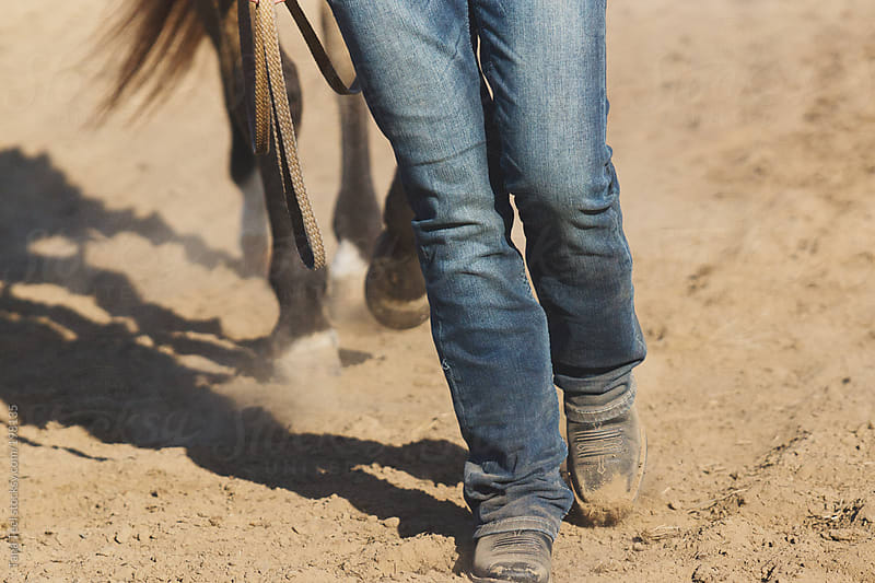 A young woman in jeans and boots leads a horse through an arena by Tana Teel for Stocksy United