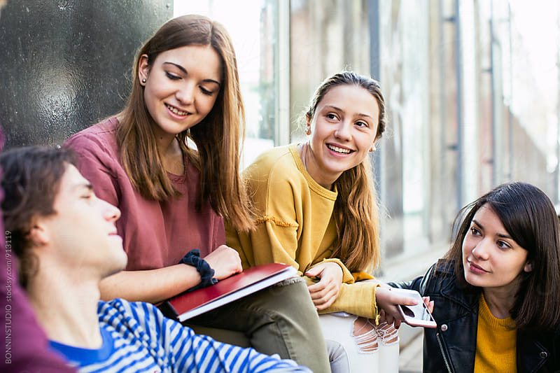 Group of teen students talking on the street. by BONNINSTUDIO for Stocksy United