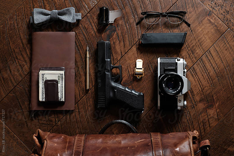 The contents of a man's briefcase laid out on a wood table by Riley J.B. for Stocksy United