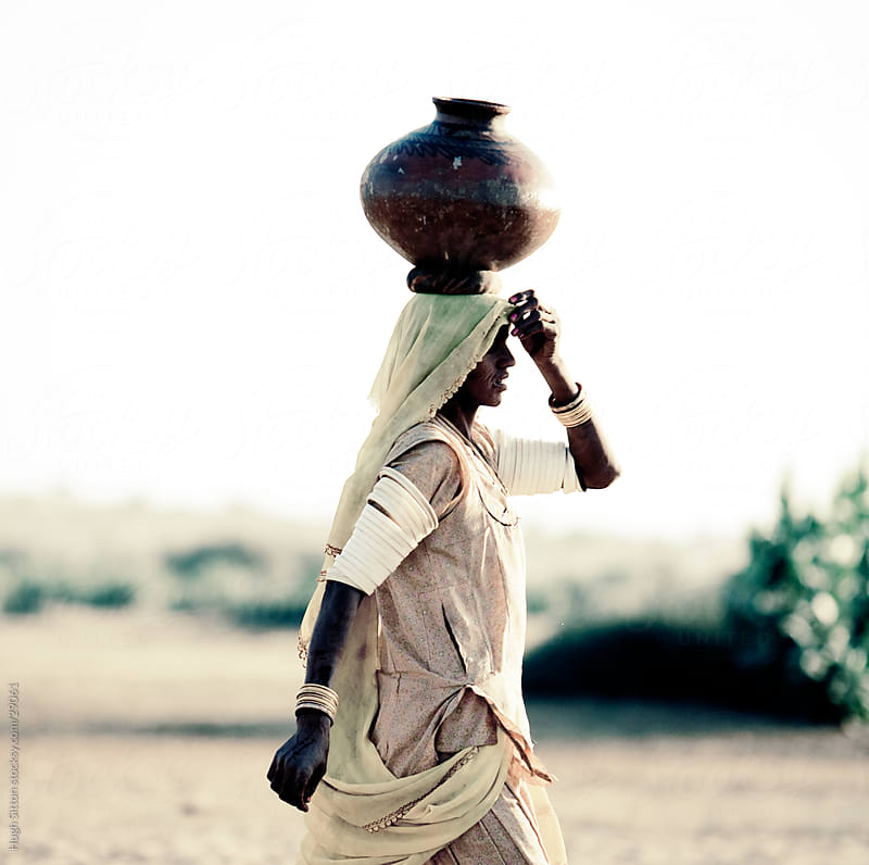 Indian woman carrying waterpot from communal well to her home. by Hugh Sitton for Stocksy United