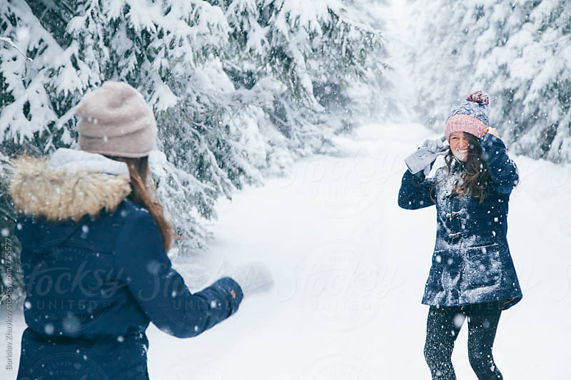 Joyful girlfriends having fun in the snow by Borislav Zhuykov for Stocksy United