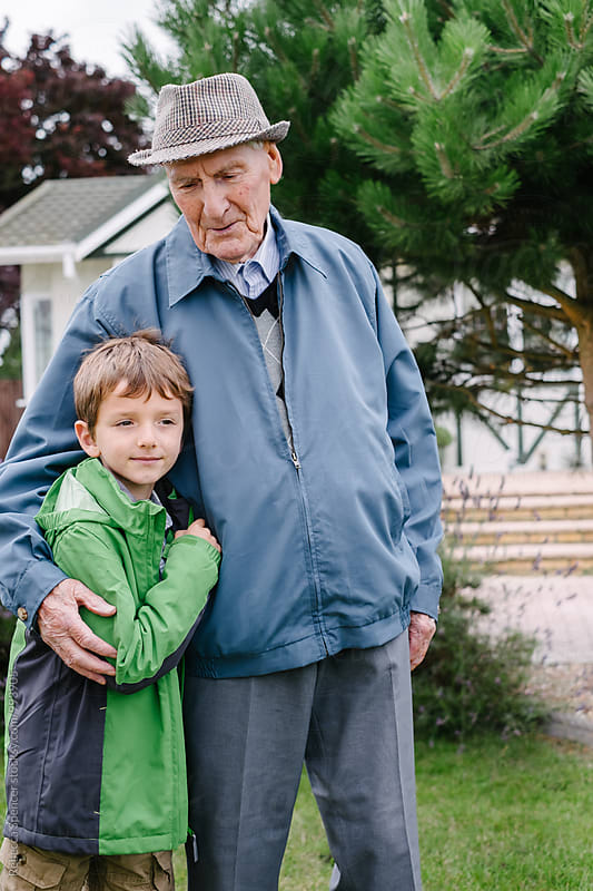 Grandson hugs his beloved grandfather by Rebecca Spencer for Stocksy United