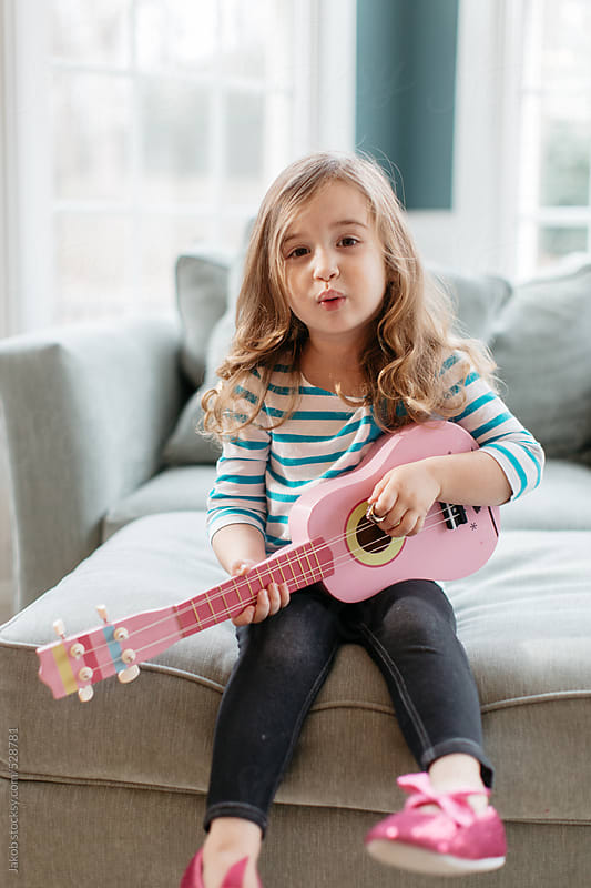 Cute toddler playing a toy guitar and singing a song by Jakob for Stocksy United