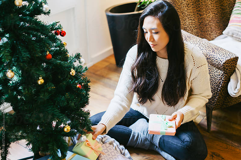 Asian woman putting presents under the Christmas tree. by BONNINSTUDIO for Stocksy United