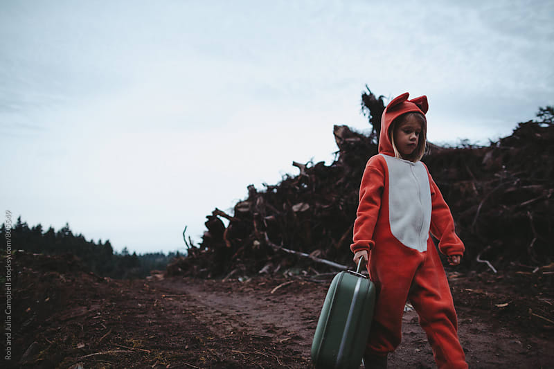 Child in fox costume walking with suitcase near logging site by Rob and Julia Campbell for Stocksy United