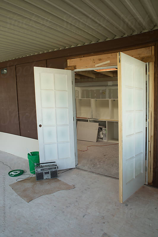 construction site of doors opening onto living room by Tanya Constantine for Stocksy United