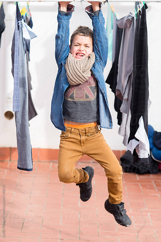 Funny boy having fun hanging on clothesline. by Guille Faingold for Stocksy United