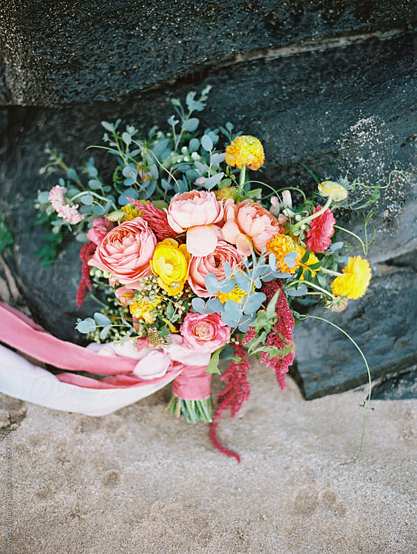 brightly colored wedding bouquet on sand and rocks by wendy laurel for Stocksy United
