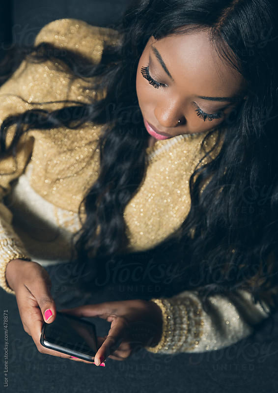 Young attractive black woman reading from her mobile phone by Lior + Lone for Stocksy United