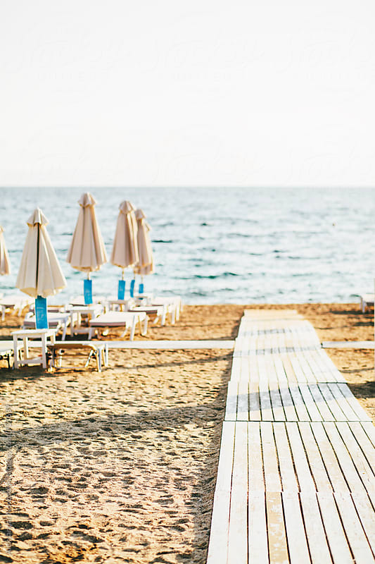 Beach with umbrellas and sunbeds in Greece by Aleksandar Novoselski for Stocksy United