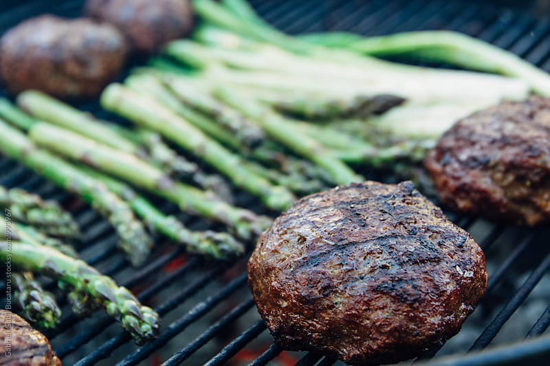 Hamburgers and asparagus on a charcoal grill by Gabriel (Gabi) Bucataru for Stocksy United