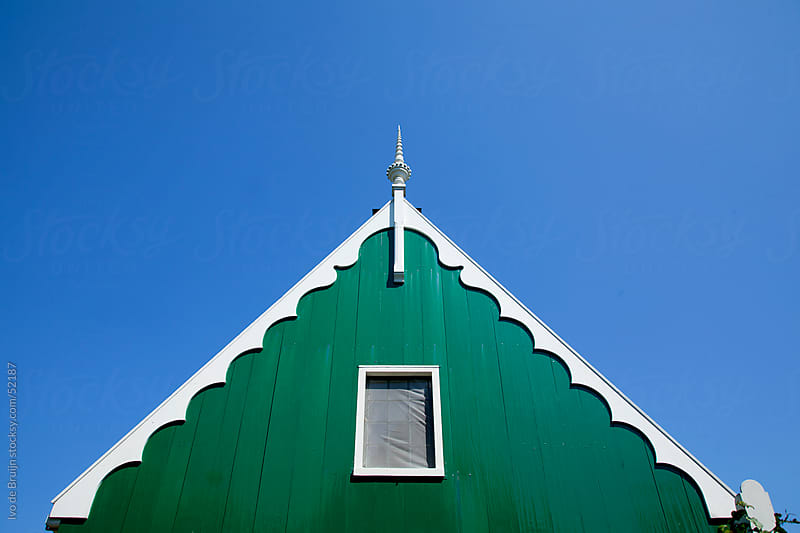 Facade of a dutch house made of wood painted in green and white, in the clear blue sky by Ivo de Bruijn for Stocksy United