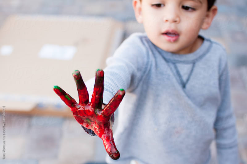 boy with red paint on his hand by Tara Romasanta for Stocksy United