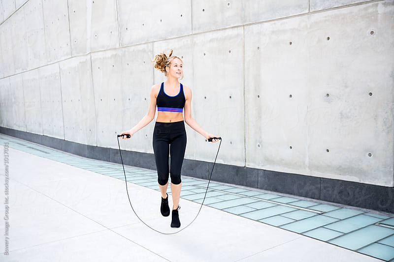 Woman skipping rope on a sidewalk by Ann-Sophie Fjelloe-Jensen for Stocksy United