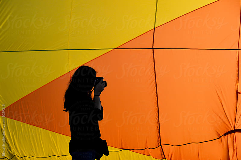 Woman taking pictures with a hot air balloon on the background by Bisual Studio for Stocksy United