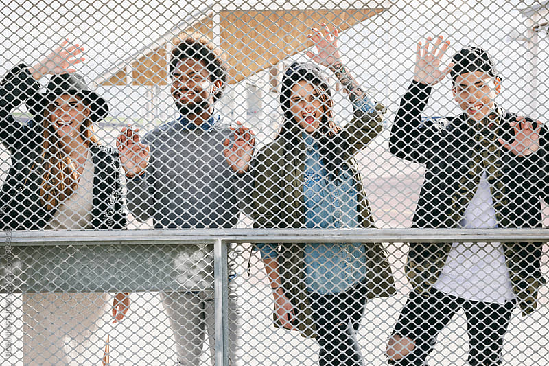 Group of multicultural friends having fun standing through a fence. by BONNINSTUDIO for Stocksy United