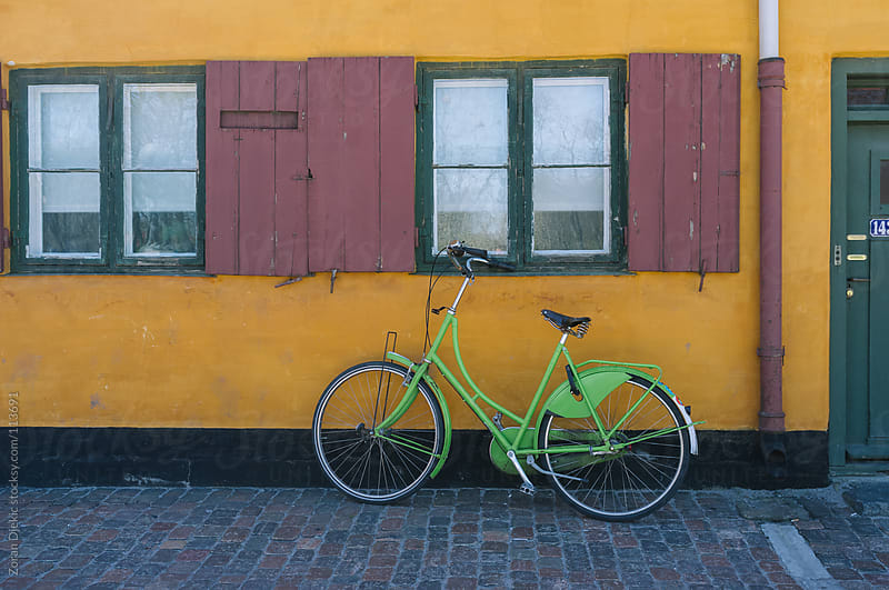 Green bicycle against a yellow wall by Zocky for Stocksy United