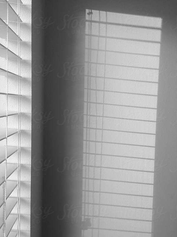 Black and white silhouette of window blinds on the wall from light in the window by Mihael Blikshteyn for Stocksy United