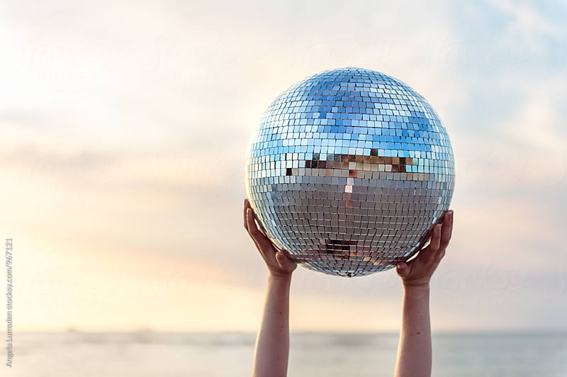Hands holding aloft a large mirrored disco ball at the beach at sunset by Angela Lumsden for Stocksy United