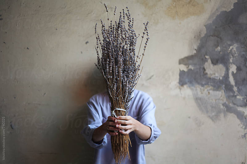 Woman holding a bouquet of lavender flowers in front of her face by VeaVea for Stocksy United