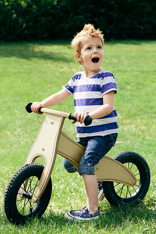 Excited young boy riding a bike on the grass by Ania Boniecka for Stocksy United