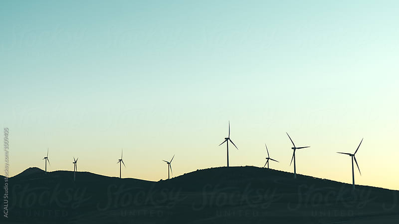 Group of windmills at sunset by ACALU Studio for Stocksy United