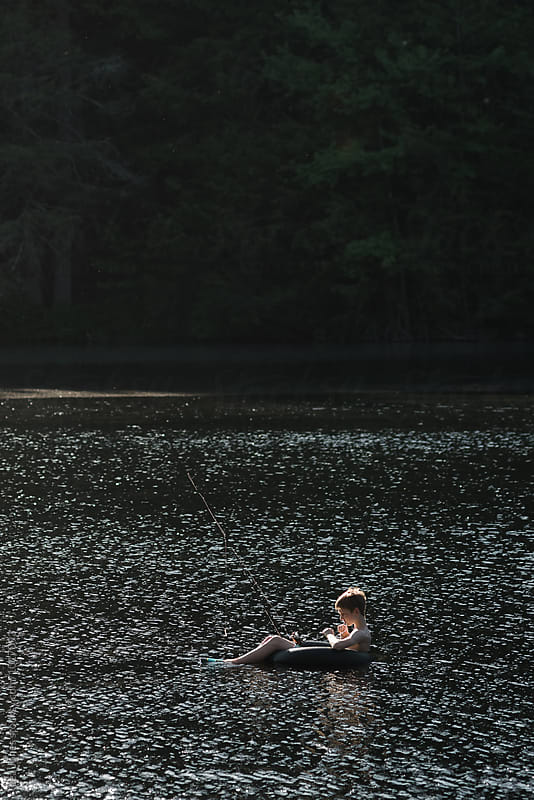 child on float in lake with fishing rod by Léa Jones for Stocksy United