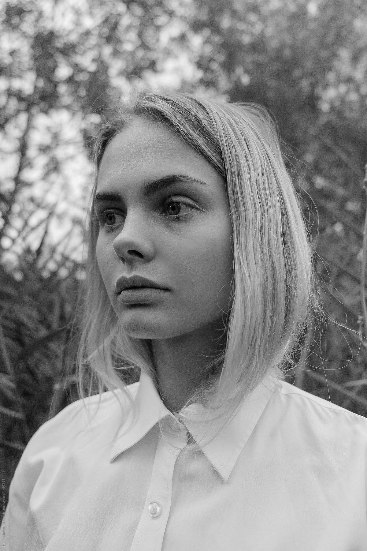 Black and white portrait of a beautiful sad blonde girl in white shirt on a background of bushes