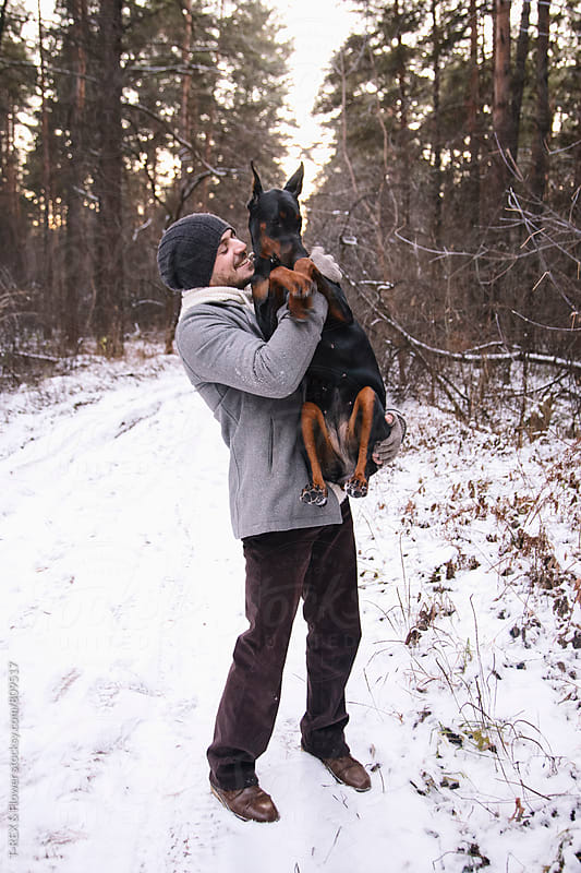 Handsome man holding his dog in arms and smiling by Danil Nevsky for Stocksy United