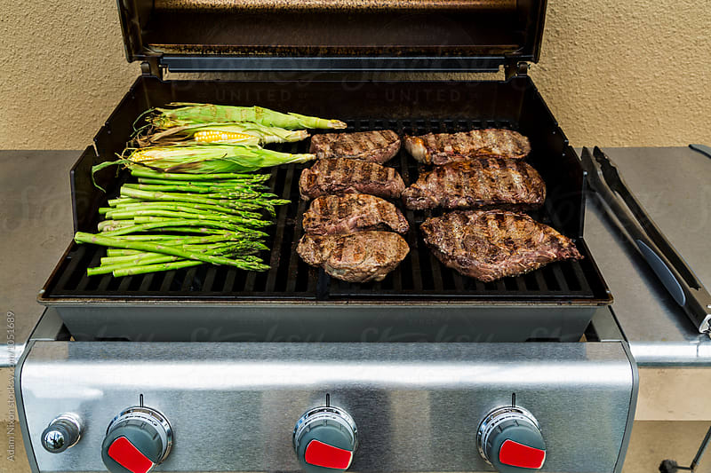 Grilling steaks, asparagus and corn on the cob by Adam Nixon for Stocksy United