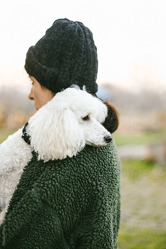 Woman holding her white poodle on the shoulder  by Marija Kovac for Stocksy United