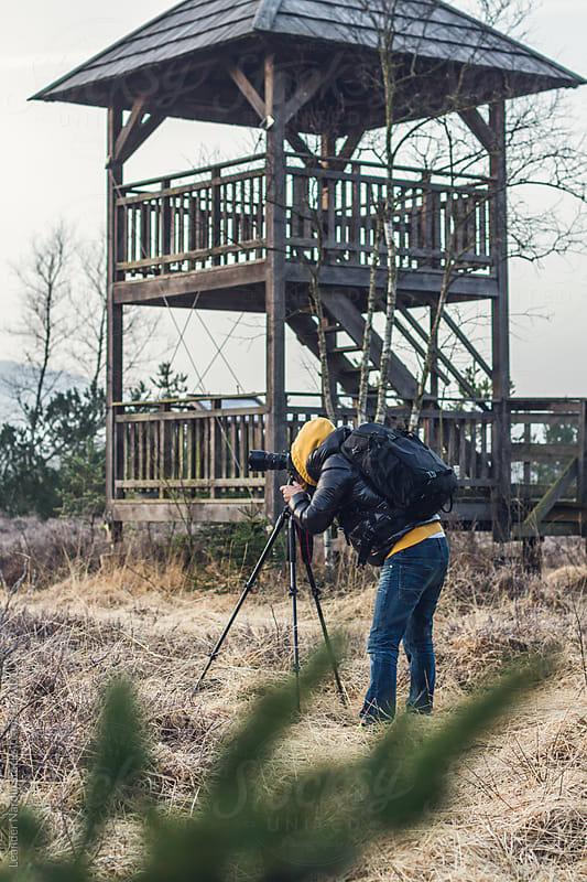 man taking photos in moor landscape by Leander Nardin for Stocksy United
