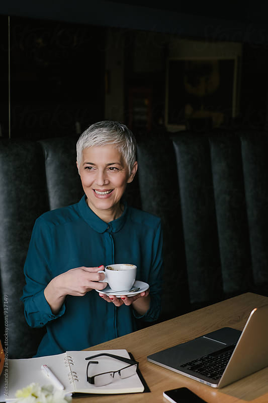 Smiling Senior Businesswoman Drinking Coffee at the Cafe by Aleksandra Jankovic for Stocksy United