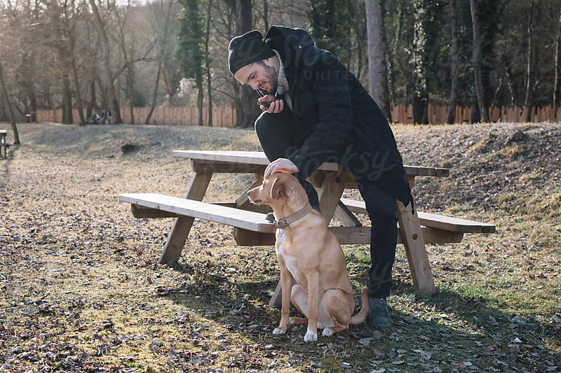 Bearded man in hat stroking brown dog by Alberto Bogo for Stocksy United