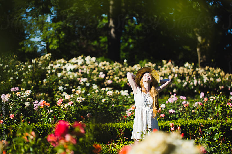 Young woman relaxing in a garden of roses by michela ravasio for Stocksy United