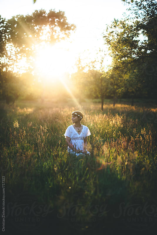 A woman with a flower crown is sitting in a meadow by Christian Zielecki for Stocksy United