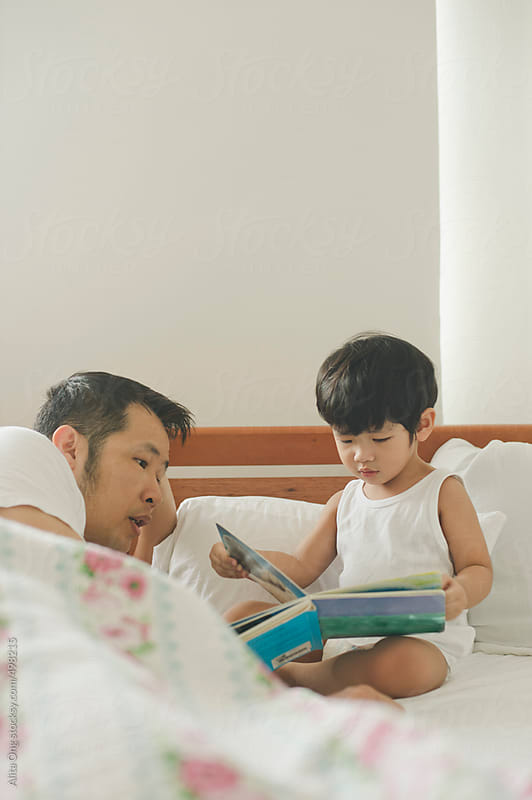 Dad and toddler reading in bedroom by Alita Ong for Stocksy United