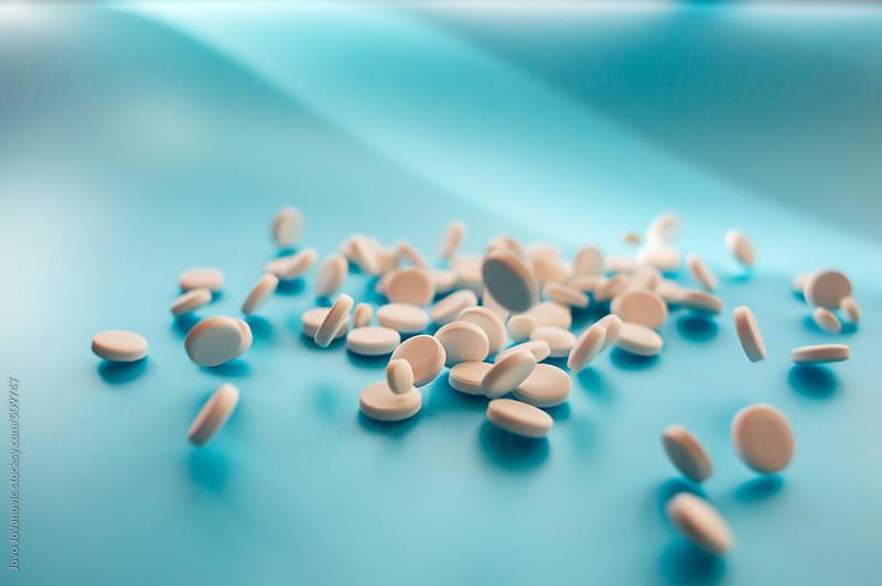 White pills on blue background by Jovo Jovanovic for Stocksy United