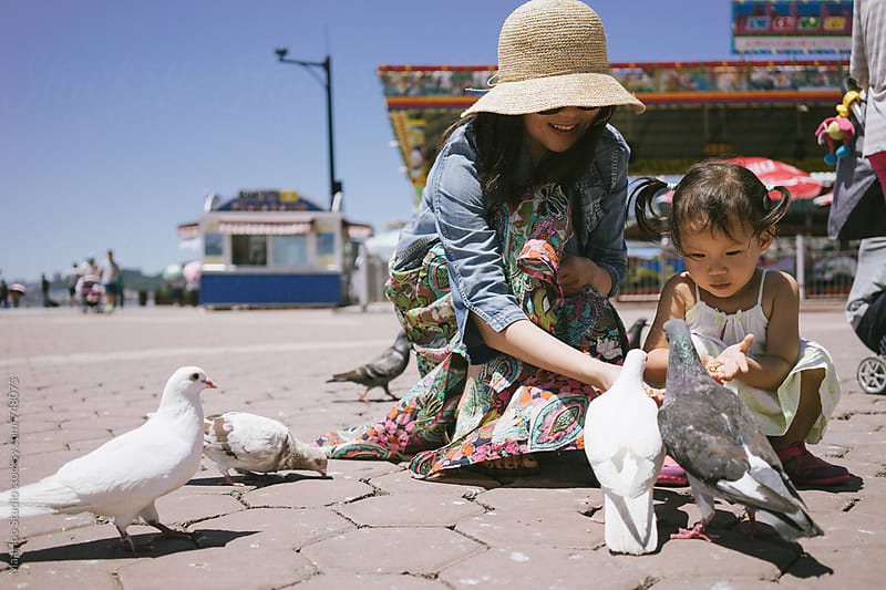 mother and daughter feeding sea gulls by Maa Hoo for Stocksy United