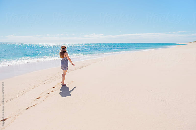 Girl walking along a prisitne beach on the Ningaloo Coast in Western Australia by Angela Lumsden for Stocksy United