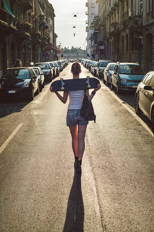 Skater girl walking in the city at sunset by GIC for Stocksy United