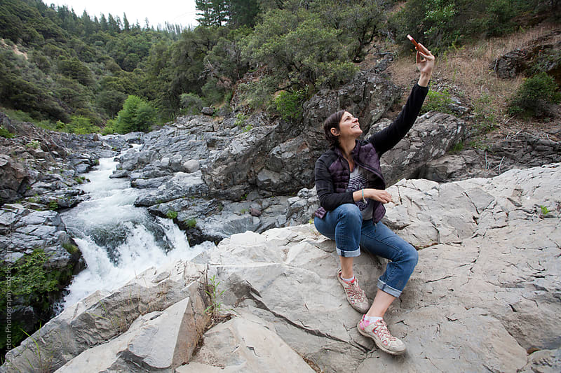 Woman taking a selfie on a rock above a waterfall  by Carleton Photography for Stocksy United