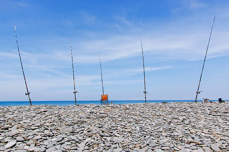 Many fishing rods on the beach   by Lawren Lu for Stocksy United