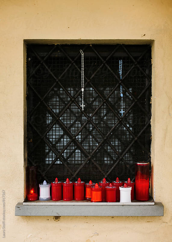 Votive candles and rosary on ancient church windowsill in northern Italy by Laura Stolfi for Stocksy United
