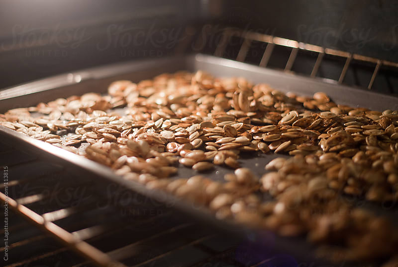 Roasting pumpkin seeds in the oven by Carolyn Lagattuta for Stocksy United